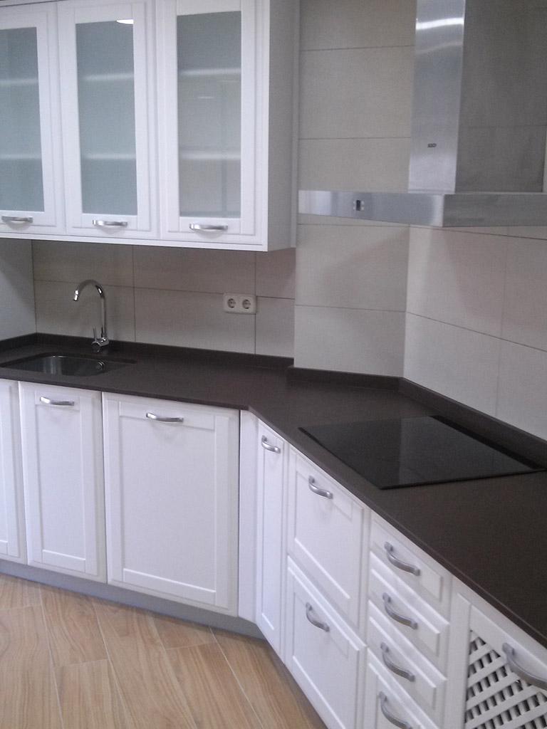 Muebles blancos premarcados y encimera de silestone en cocina