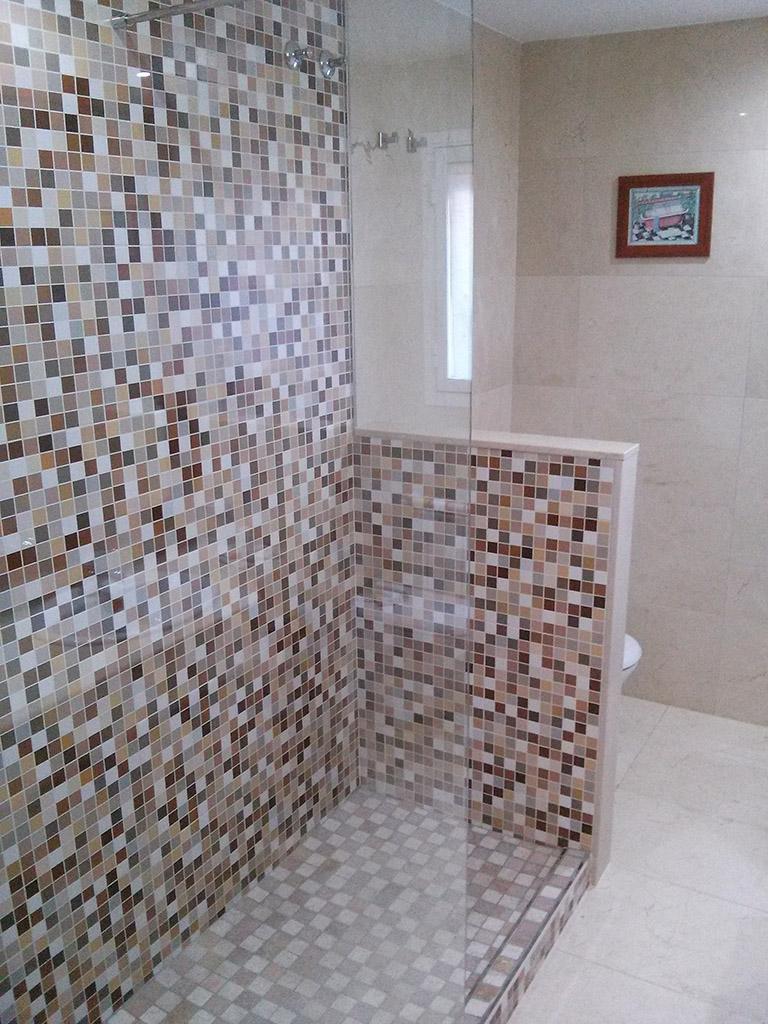 Detalle de ducha de gresite y manpara de cristal