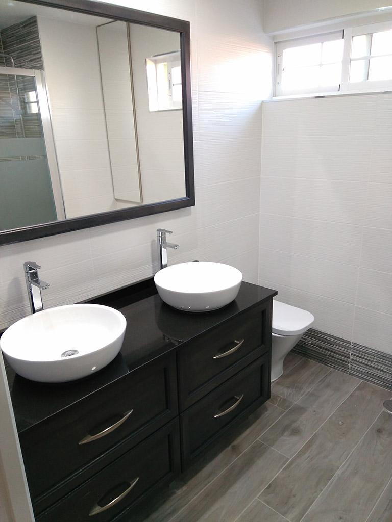 Mueble bajolavabo en madera y tapa de granito negra para baño