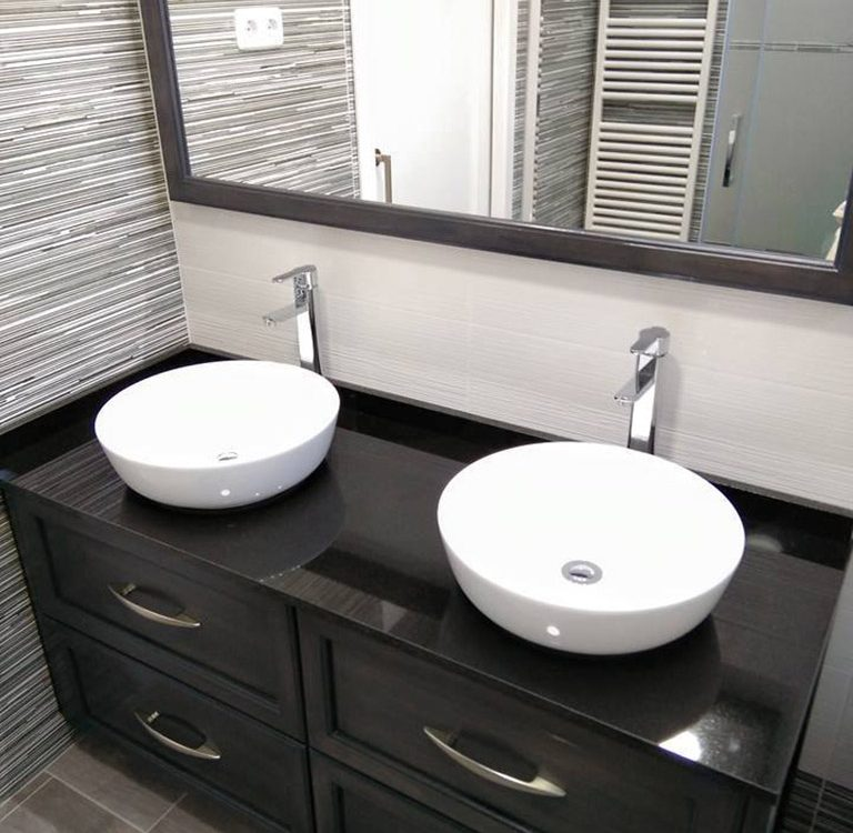 Lavabos redondos sobre mueble de baño oscuro