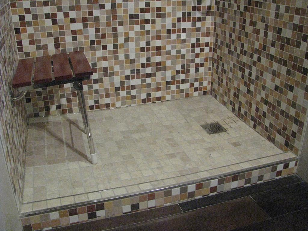 Detalle de plato de ducha de obra con asiento integrado