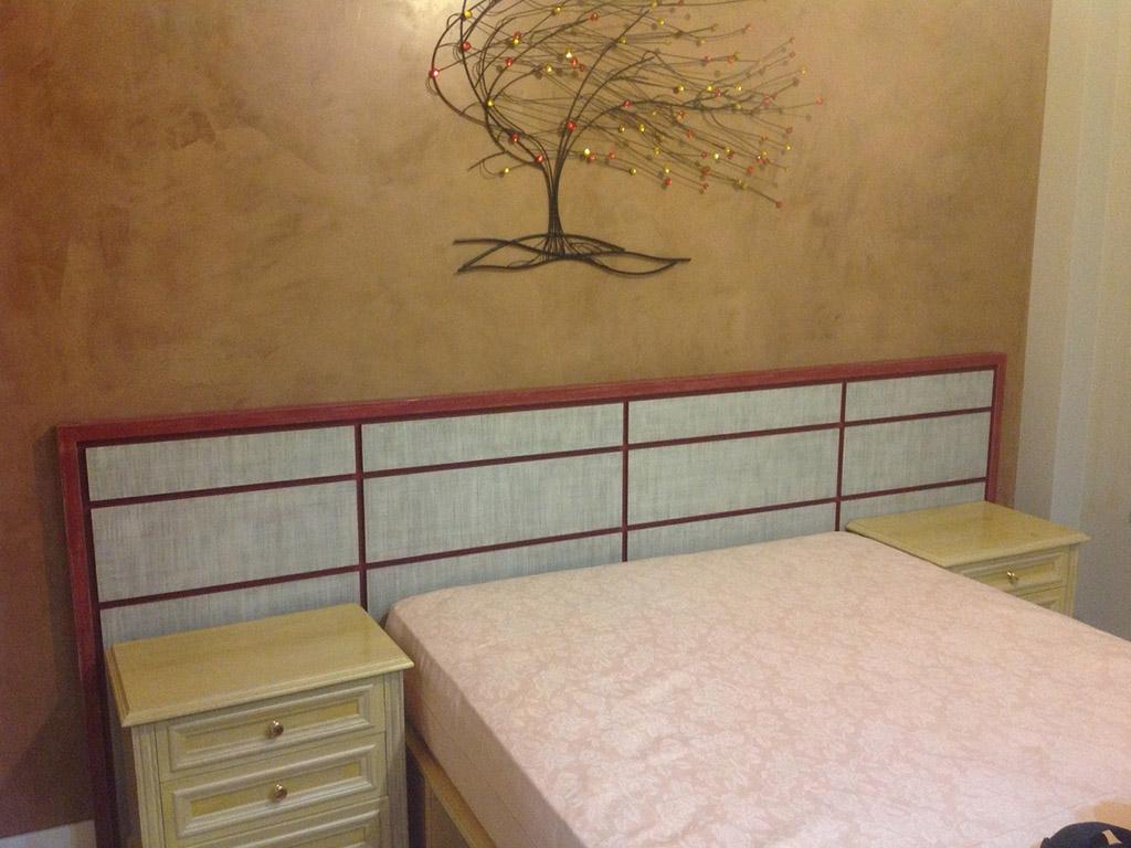Cabecero en madera y detalle decorativo en pared